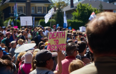 A protester holds a Death to Fascists sign at the Vancouver Stand Up to Racism Rally