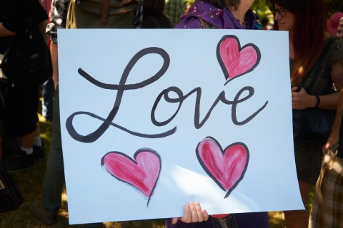 "A counter-protester holds a sign saying ""love"" at the Vancouver Stand Up To Racism Rally"